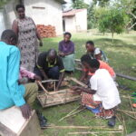 LINK Finalist team member Jeniffer Tumwine instructing community members on how to construct low-cost hives.