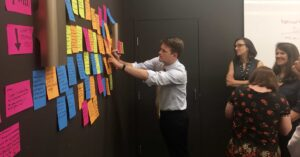 A participant adds sticky notes to the wall to contribute to the exercise known as challenge mapping
